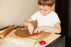 Children`s hands make gingerbread. Small boy cutting cookies for Royalty Free Stock Photo