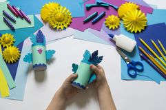 Children`s hands make a parrot of colored paper. Toy origami bird. Glue, scissors and paper on a white background. Children`s art project for children. Craft stock images