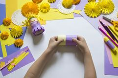 Children`s hands make a princess of paper. Handy for a party. A gift for the Mother`s Day holiday. Master Class. Kindergarten. Materials for creativity royalty free stock photo