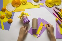Children`s hands make a princess of paper. Handy for a party. A gift for the Mother`s Day holiday. Master Class. Kindergarten. Materials for creativity royalty free stock images