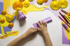Children`s hands make a princess of paper. Handy for a party. A gift for the Mother`s Day holiday. Master Class. Kindergarten. Materials for creativity royalty free stock photography