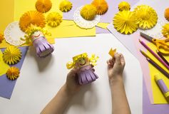 Children`s hands make a princess of paper. Handy for a party. A gift for the Mother`s Day holiday. Master Class. Kindergarten. Materials for creativity stock images