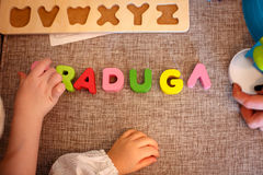 Children's hands make up the word. Child hands writing word RADUGA on the tissue stock photo