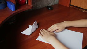 Children's hands making origami plane stock video