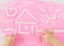 Children`s hands paint a beautiful picture on decorative sand. Stock Photo
