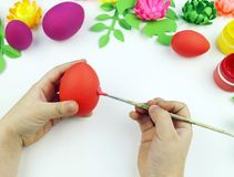 Children`s hands paint Easter eggs. The child is drawing. Easter. Preparation for the Easter party.Paper flowers and leaves royalty free stock photos