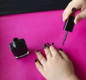 Children`s hands paint their nails with black nail polish. children`s manicure. black manicure on childish nails. Children`s manicure. Children`s hands paint stock photos