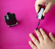 Children`s hands paint their nails with black nail polish. children`s manicure. black manicure on childish nails. Children`s manicure. Children`s hands paint royalty free stock image