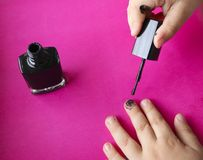 Children`s hands paint their nails with black nail polish. children`s manicure. black manicure on childish nails. Children`s manicure. Children`s hands paint stock image