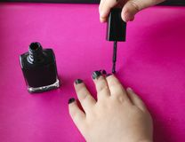 Children`s hands paint their nails with black nail polish. children`s manicure. black manicure on childish nails. Children`s manicure. Children`s hands paint stock photography