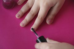 Children`s hands paint their nails with pink shiny nail polish. Children`s manicure. children`s hands paint their nails with pink shiny nail polish. glamorous stock image