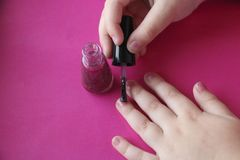 Children`s hands paint their nails with pink shiny nail polish. Children`s manicure. children`s hands paint their nails with pink shiny nail polish. glamorous royalty free stock image
