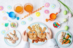 Children's hands with pancakes, sweets and juice for Easter. stock photography