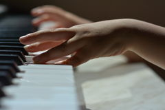 Children's hands on the piano keys Stock Image