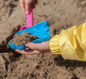 Children's hands playing with sand in a sandbox Stock Image