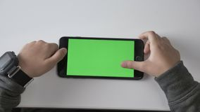 Children`s hands playing on a smartphone, Green screen, chromakey concept, Top shot 60 fps. Children`s hands playing on a smartphone, Green screen, chromakey stock video footage