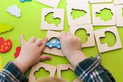 Children`s hands playing with wooden shape sorter Stock Photos