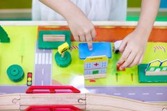 Children`s hands playing wooden toy train stock image
