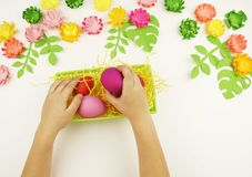 Children`s hands put Easter eggs in a green basket. Easter. Preparation for the Easter party. royalty free stock image