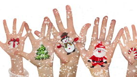 Children's hands raising up with painted Christmas symbols stock footage