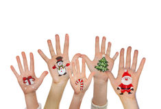 Children's hands raising up with painted Christmas symbols Royalty Free Stock Photography