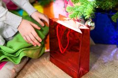 Children`s hands reaching out for red Christmas gift bag under the green tree. Children`s hands reaching out for red Christmas gift bag under the tree Stock Image