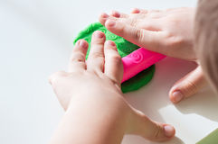 Children's hands with rolling-pin playing modeling clay. Royalty Free Stock Photos