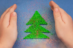 Children`s hands to protect Christmas tree cut from plush sprinkled with glitter Stock Image