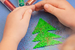 Children`s hands to protect Christmas tree cut from plush sprinkled with glitter Royalty Free Stock Photos