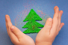 Children`s hands to protect Christmas tree cut from plush sprinkled with glitter Stock Photos
