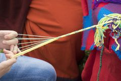 Children& x27;s hands weave a yarn. From a yarn. Weaving belts is one of the popular and accessible types of needlework Stock Image
