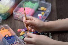 children's hands are weaving figures out of colored rubbers Royalty Free Stock Photos
