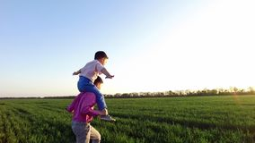 Children`s happiness, two little brothers are having fun. Carefree childhood. Summer evening, at sunset, in the rays of the sun, through the thick green grass stock footage