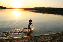 Children's happyness. Boy running on the evening beach Stock Photography