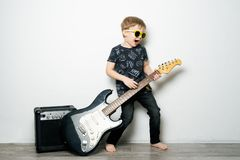 Free Children`s Hobbies: A Little Boy In Black Glasses Plays The Electric Guitar, Imitates A Rock Star. Royalty Free Stock Images - 139920109