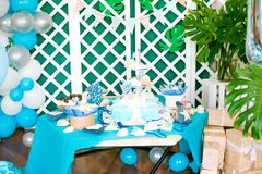 The children`s holiday is decorated with blue balloons, seashells, and green plants, a beautiful candy bar with a blue cake. For a small birthday in a marine Stock Photos