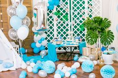 The children`s holiday is decorated with blue balloons, seashells, and green plants, a beautiful candy bar with a blue cake. For a small birthday in a marine Royalty Free Stock Photography