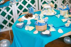 The children`s holiday is decorated with blue balloons, seashells, and green plants, a beautiful candy bar with a blue cake. For a small birthday in a marine Stock Photography