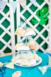The children`s holiday is decorated with blue balloons, seashells, and green plants, a beautiful candy bar with a blue cake. For a small birthday in a marine Stock Photo