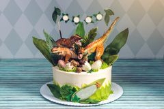 Children's holiday white cake decorated with dinosaurs in the Jurassic period jungle. Concept ideas desserts for kids