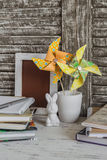 Children's home workspace with books, notebooks, notepads and handmade paper pinwheels Stock Photos