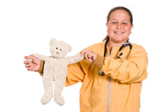 Children's Hospital. A young girl holding up a stuffed bear while wearing a stethoscope, isolated against a white background Stock Photos