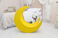 Children's interior. White light room with a cot, the moon toy, a Teddy bear. Stock Photo