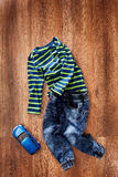 Children`s jacket and jeans with blue toy car on a wooden background. Royalty Free Stock Image