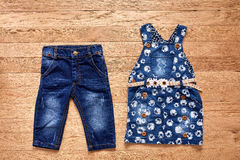 Children`s jeans denim dress on wooden background. Royalty Free Stock Image