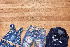 Children`s jeans, jacket and denim dress on wooden background. Royalty Free Stock Photos