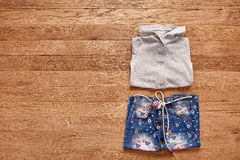 Children`s jeans and jacket on wooden background. Royalty Free Stock Photography