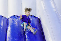 Children's joy of entertainment. Boy slides down an inflatable slide Royalty Free Stock Photo