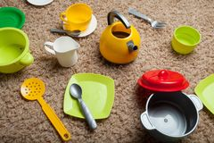 Children`s kitchen game, kettle, cups, plates, forks, spoons, saucepan. Multicolored royalty free stock images