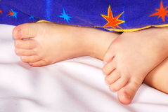 Children's legs. Stick out from under blankets Royalty Free Stock Images